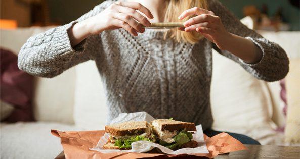 girl taking a photo of her sandwich